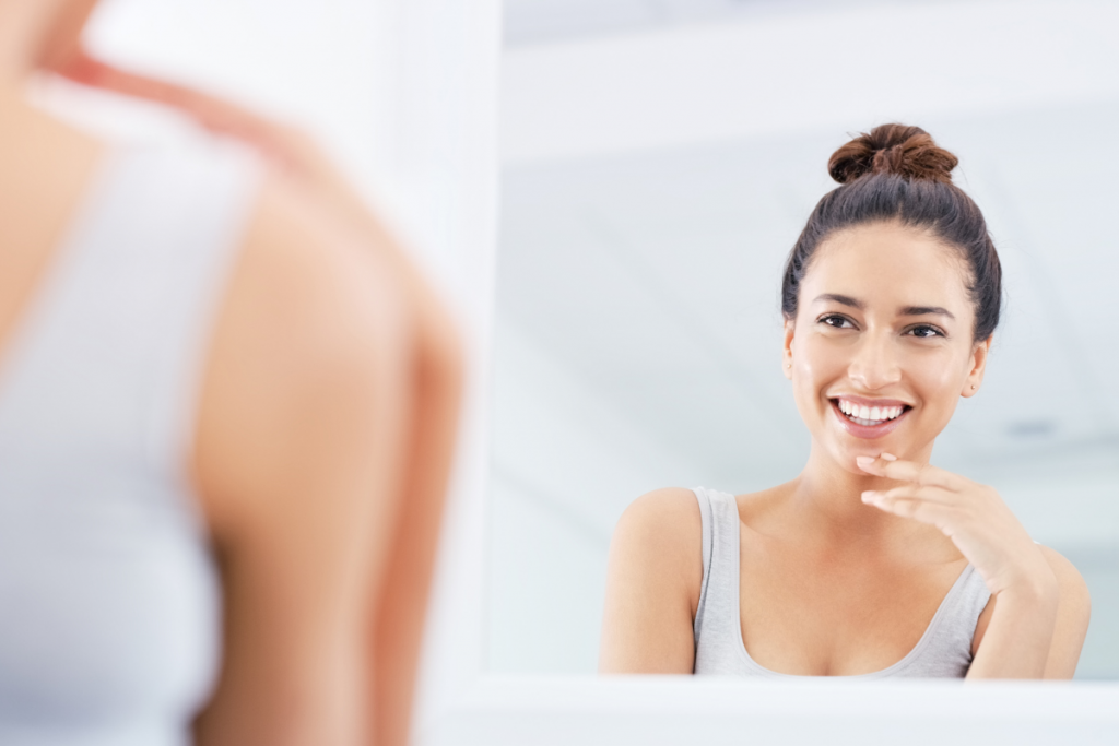 woman smiling in mirror- Get rid of acne scars at K2 Restorative Medicine